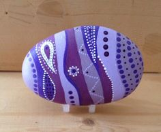 A stone painted in shades of purple with white highlights. Hand painted on stone using acrylics and finished with a gloss sealant. Unique and individual paperweight or simple home decorative piece. Can be bought with or without stand. Approx 10m at widest  Comes in voile drawstring pouch.  NB Although it is protected in external sealant, it is only recommended for indoor use.