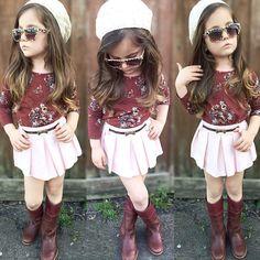 Niña usando un falda rosa con blusa y botas rojas recargada sobre una pared