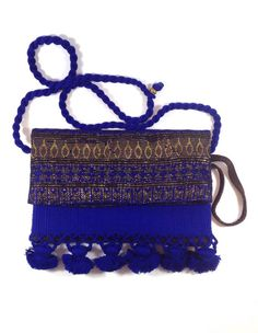 Guatemalan Textile clutch, made with genuine leather, and blue and gold textile. Beautiful clutch with tassels. Removable crossbody strap. Perfect bag for fall and winter. Available at www.shopkokay.com $90 #guatemala #clutch #fall