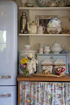 smeg fridge in blue, vintage style utility area in English country cottage with collections of kitchenalia on show. Reclaimed wood workstops, curtains hide the washing machine and dish washer.