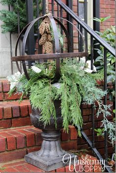 Fill an urn with evergreen branches and a metal orb with magnolia blossom cones hanging inside