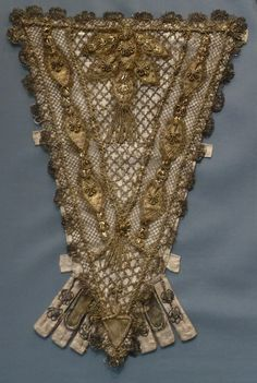 Stomacher, France, Silk satin with metallic-thread lace, appliqués, passementerie and tassels. A stomacher is a decorated triangular panel that fills in the front opening of a woman's gown or bodice.