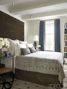 The bed in the master bedroom is dressed with linens by E. Braun & Co. and a coverlet and pillows of indigo silk ikat; the vintage stool is by Thonet, and the headboard is upholstered in a Pollack fabric. - ELLEDecor.com