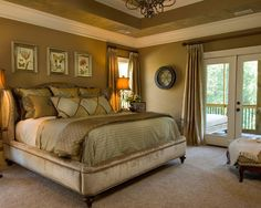 Nice looking bedroom with hand painted, framed prints above the bed, covered bed frame and headboard which matches the carpet and tall ceiling with the same colors of light and darker brown paint. Nice doorway out to a large deck or balcony area.