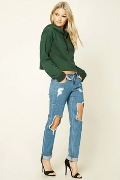 A pair of mid-rise jeans featuring a distressed design, five-pocket construction, cuffed hem, and a zip fly.