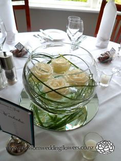 "Modern and sleek.... for the Bride who wants to have the ""Wow!"" in her wedding come from the bridal party's flowers. We can do these using roses in any shade... ornamental grass is looped inside of the (Rented to you) bubble glass vase... four votives included as well as the mirror the arrangement sits upon."