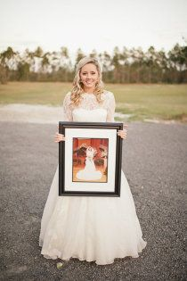 Bride holding a picture of the mother of the bride on her wedding day.