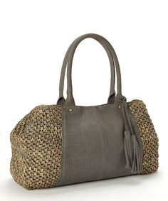 Keep essential gear close at hand with this stylish tote. Its raffia and leather construction gives it rustic charm, while a roomy interior makes for a fashionably functional pick.