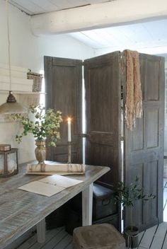 Salvaged doors, hinged together, act as a room divider.