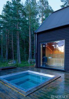 Implantée sur une terrasse en bois, le bleu de cette mini piscine contraste avec la verdure de la forêt à proximité.