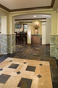 A grand entrance to this lower level highlights custom arches, stone tile floors and wood trim