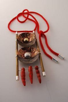 Constructed of found rusted steel,gilding metal,brass,bamboo,s/silver,red coral and red cord.  Neckpiece