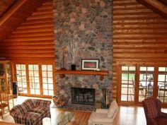 Soaring fieldstone fireplace belongs to a full log retreat on 187 acres:)