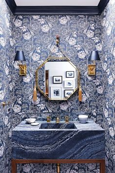 The powder room features Peony wallpaper by Farrow & Ball. The custom-made brass mirror is flanked by two sconces by Ralph Lauren.