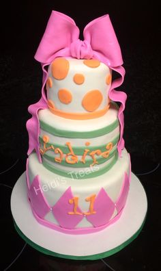 Girly pink, orange and green cake with diamonds, stripes and polka dots with a fondant bow with ribbon.