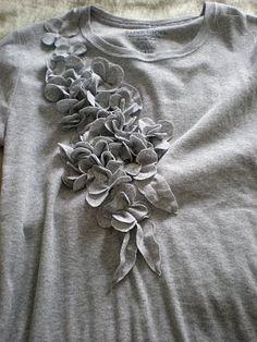 1) Pegue um tecido, dobre ao meio e corte em um formato parecido com o formato da foto acima 2) Corte vários pedaços. 3) Costure as flores ...