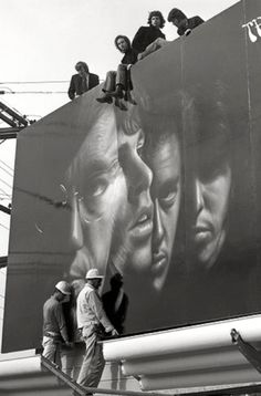 The Doors, atop their Sunset Strip billboard (1967) | iconic | 1960s | jim morrison | 27 club | fame | black & white | vintage | music |