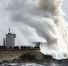 People look on as high waves strike the harbor wall at Porthcawl, Wales, on Feb. 8, 2014. Strong winds and heavy rain continue to lash the southwest of England and south Wales with winds gusting at up to 80 mph in places.