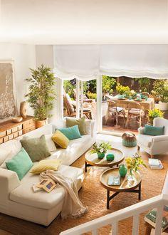 Salón en crudo con cojines en verdes y mesitas redondas 00405964