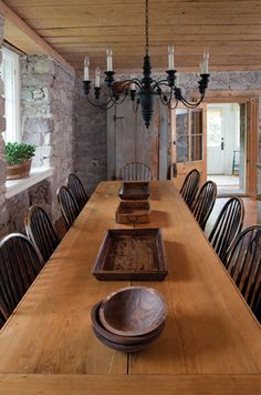 The 14-foot harvest table, made from planks from the original tamarack floors, seats the owners' 12 grandchildren. A classic blue Quebecois chandelier was painted black to coordinate with the distress