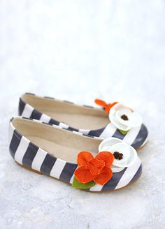 Graphic blue and white stripes pair together with double flowers in chiffon and pumpkin with felt leaves.  These happy little skimmers are glazed for durability and have eco cotton insoles.  Includes a matching clip!