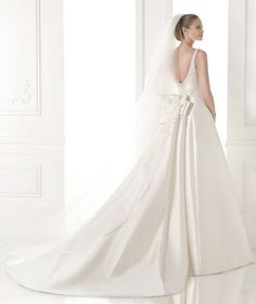 A-line mikado silk dress. Bateau bodice with pearl appliqués. Low back and detachable train with bow at the waist.