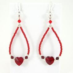 Exquisite ruby-red drop-shaped earrings with sterling silver fish hook earwires, ruby-red 10mm swarovski crystal hearts which are surrounded by sterling silver beads 3 and 6mm, and 4mm siam-red swarovski crystals.   The length of the earrings is almost 3 inches.  http://www.beadedjewels.biz/special_occasions.html