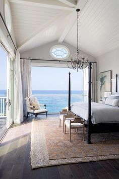 A+poster+bed+sits+in+the+center+of+this+bedroom+complete+with+doors+that+open+up+to+the+ocean.+
