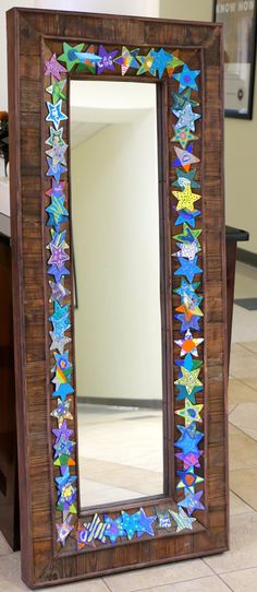 Third grade collaborative art project. Mirror was generously donated by Carolina Pottery. Students painted wood stars during a recess period.