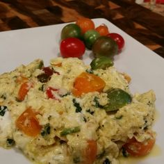 Scrambled eggs in olive oil with spinach, cherry tomatoes, goat cheese, and a squeeze of lemon.