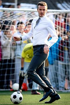 David Beckham playing soccer in a suit!