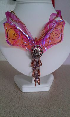 Pink ribbon and gold crotchet beading thread necklace. Fusion film and wire wings, Tim Holtz findings and homemade jump rings. And clear Quartz and Amethyst gemstones.