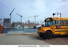 Helsingborg, Sweden - 10 April, 2018: Yellow Thomas Bus parked at Helsingborg waterfront with background of large construction site with several cranes building new complex in city center