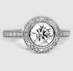 An intricate halo of pavé-set diamonds embraces the center bezel set diamond of this gorgeous antique-style ring.