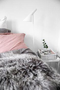 Cozy scandinavian bedroom with pink bedding and grey fur throw. Image by Kiki via Damernas Värld