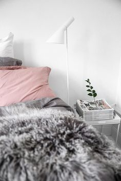 Cozy scandinavian bedroom with pink bedding and grey fur throw. Image by Kiki via Damernas Värld