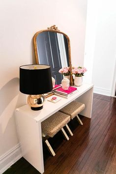 Chic foyer features a pair of leopard print stools tucked under a white console table, Ikea bookcase hack, topped with a gold lamp with black shade, coffee table books Crate & Barrel Rati Vase and an Anthropologie Gleaming Primrose Mirror.