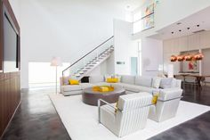 A fabulous example of a modern take on white interior with pops of canary yellow. The art upstairs is picked up in the pillows on the sectional and then again in the dining art.