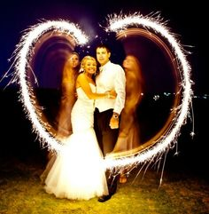 Great nighttime shot of the bride and groom behind a sparkling heart. Photography by www.chiphotographyofcharleston.com