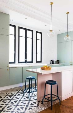 pastel candy coloured kitchen with black and white tiled floor. mint green cupboards and blush pink island. black bar stools. black framed windows. brass globe lighting.