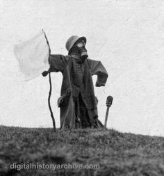 "WWI, 1918.  A surrender ""scarecrow' dressed in German trench coat, helmet, and gas mask holding a white flag,  The photograph was taken in Virton, Belgium on December 2, 1918 almost a month after the war ended."