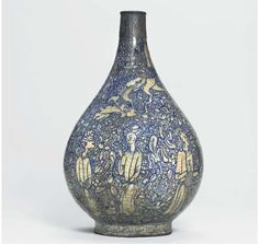 A LARGE SAFAVID BLUE AND WHITE POTTERY BOTTLE  IRAN, POSSIBLY KHORASSAN, CIRCA 1580-1600  Of pronounced drop-shape on short foot, the surface completely covered with fine scrolling motifs around a variety of human figures, animals and animal combat groups divided by similar floral sprays, the foot with a band of scrolls, the neck broken and mounted in the Qajar period with a brass band of engraved figural cartouches,   14¾in. (37.5cm.) high
