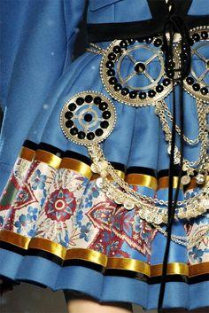 John Galliano. Pleated twill skirt(dress) ribbon hem, medallion and chain embellishments.