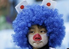 A young Japanese fan with his face painted in the Japanese colors.