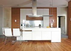 mobilier de cuisine blanc laqué, chaises design assorties et sol en parquet massif