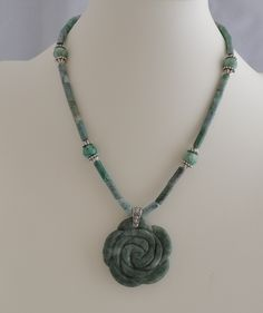 http://www.adhicreations.com/products/245-jade-n-marble-necklace.aspx  Jade N Marble Necklace  The beautiful Marble rose blooms amidst a variety of African jades. The center piece is a lovely carved flower made of marble stone. Along with 'ching hai' and African Jade, It is truly a unique and designer piece. The antiqued silver plated pewter and bead caps enhance the beauty. Make it a three piece set by adding the bracelet  set from below  Product ID : N1021  Availability: In stock  $45.00…