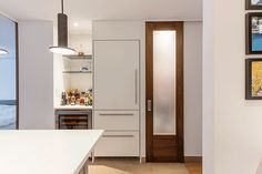 As for the old closet, Kris turned part of that into the mudroom Frans and Dalal were after, complete with custom shelving and various storage needs. And as an extension for the new kitchen, white custom cabinetry conceals the refrigerator and houses an exposed wet bar and wine fridge.