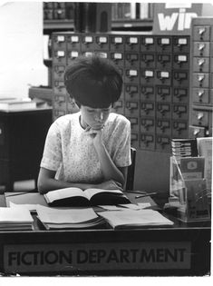 """Fiction Department 1960's [possibly in Montreal],"" by George Zimbel -- I'm loving the two catalogs behind her, one more empty than full! (Also flashing back with those white lips and eyelids...)"