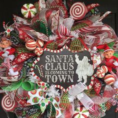 This is a fun and whimsical Christmas Deco mesh wreath. The center sign is made of metal & says Santa Clause is coming to town, with a