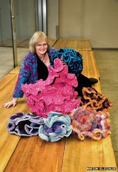 Cornell University professor Daina Taimina poses with a variety of the hyperbolic plane models she crocheted to demonstrate geometric principles for her students.